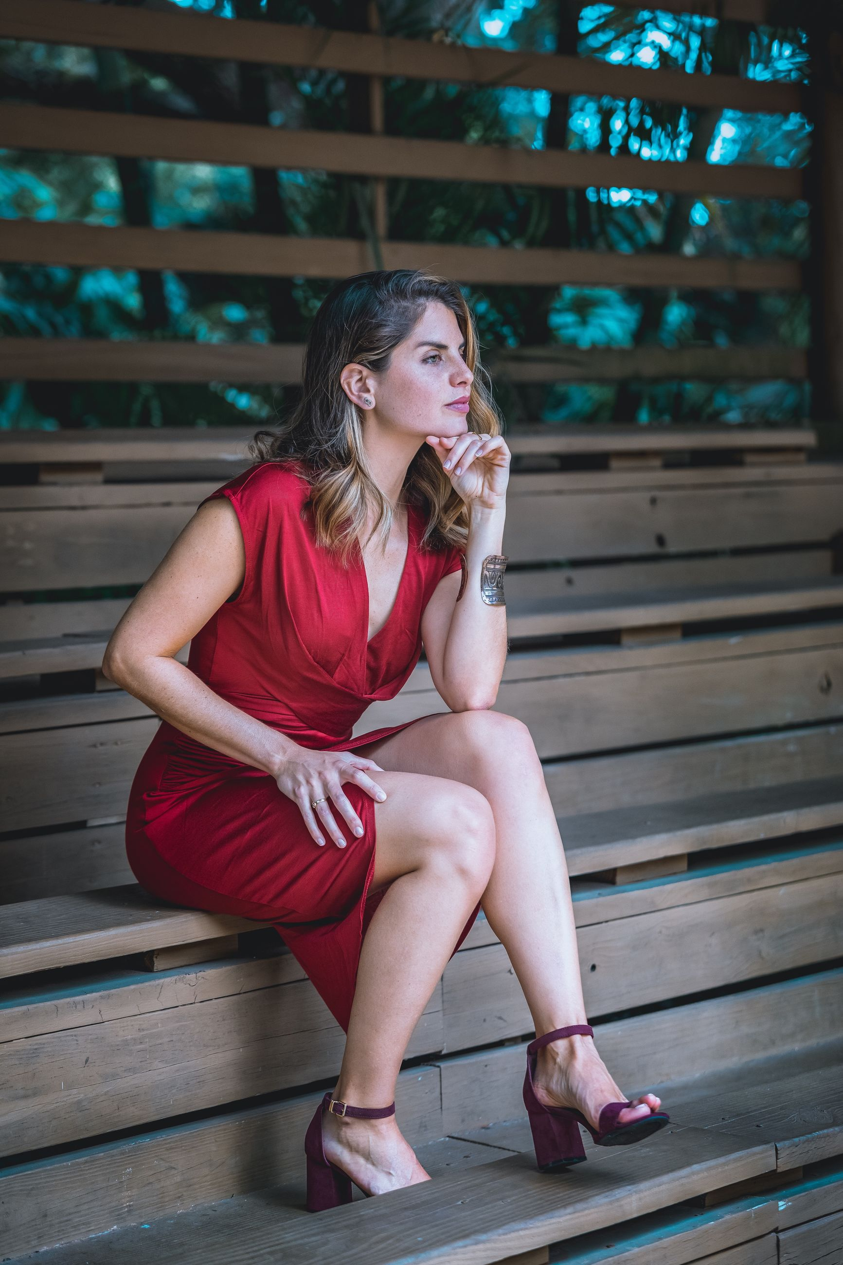 sitting, one person, real people, full length, front view, lifestyles, looking, casual clothing, young women, young adult, leisure activity, looking away, staircase, wood - material, seat, relaxation, women, adult, beautiful woman, hairstyle, contemplation