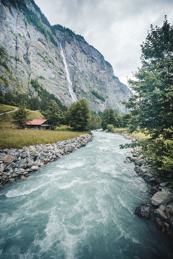 Water Rock Beauty In Nature Scenics - Nature Rock - Object Solid Motion Mountain Nature Sky Day Waterfront Flowing Water Tree Plant Waterfall Tranquility Tranquil Scene River Flowing No People Outdoors Formation Lauterbrunnen Valley Lauterbrunnen