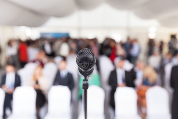 The microphone in focus against blurred audience at a business or professional event. Corporate Event Lecturing PR Unrecognizable People Audience Audience Crowd Blurred Silhouettes Business Business Conference Business Meeting Business People Communication Conference - Event Corporate Business Executive  Group Of People Managers  Managers Meeting Marketing Microphone Microphone In Focus Presentation Public Speaker Public Speech Speech