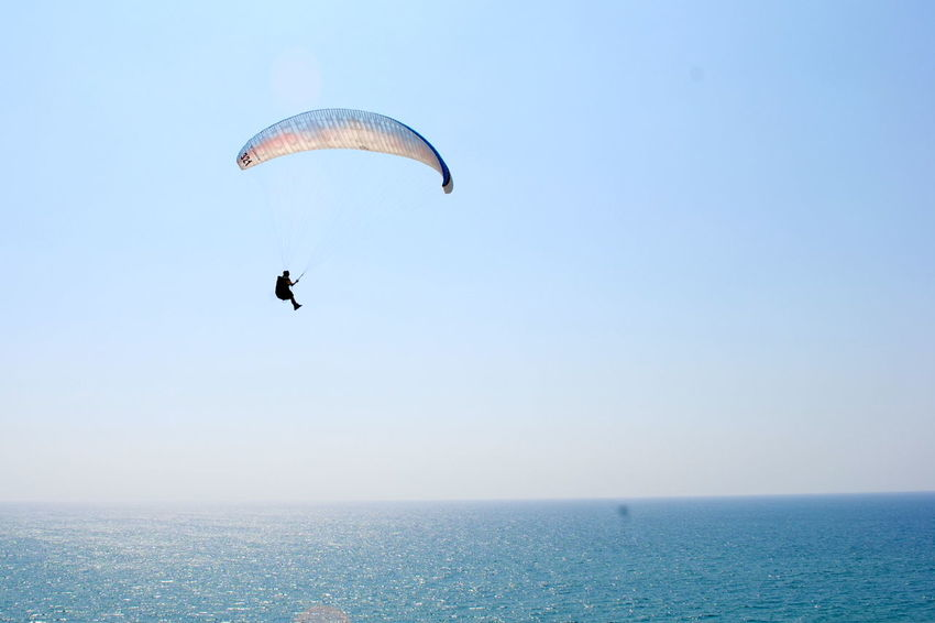 Adventure Beauty In Nature Blue Day Enjoyment Extreme Sports Flying Freedom Fun Leisure Activity Lifestyles Mid-air Nature Outdoors Parachute Paragliding Scenics Sea Sky Sport Tranquil Scene Tranquility Unrecognizable Person Vacations Water