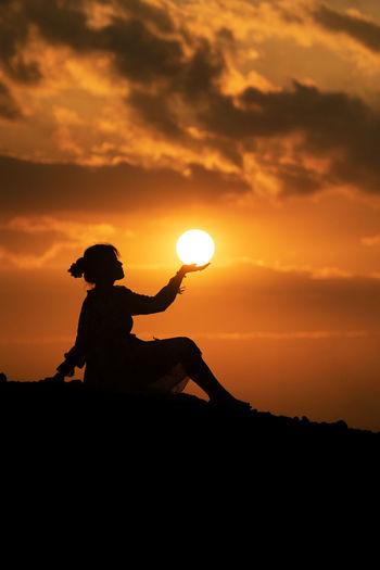 Silhouette man against orange sky during sunset