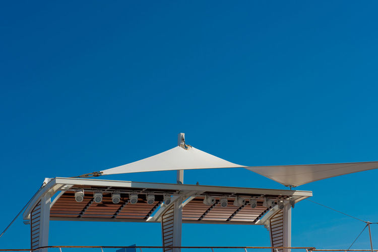 Low angle view of awning against clear blue sky