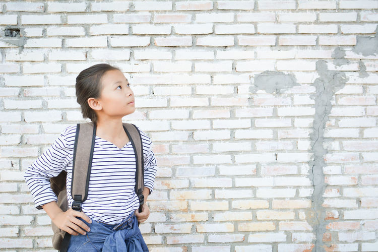 Young girl standing against brick wall