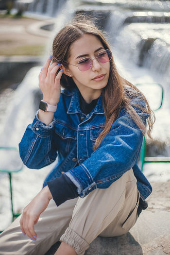 Young woman wearing sunglasses looking away while sitting outdoors
