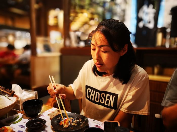 The girl looks at the food that is full of satiety.