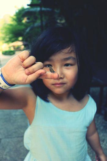 Portrait of cute girl showing butterfly on finger