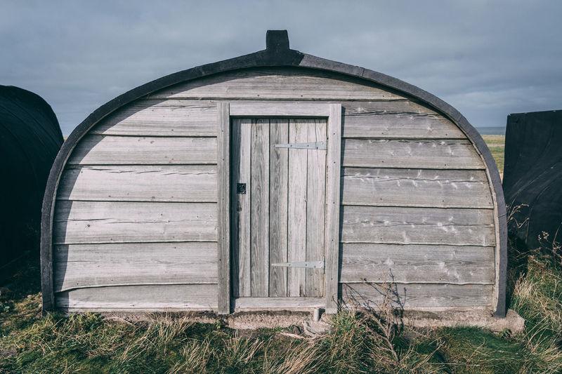 Closed wooden door on field against sky