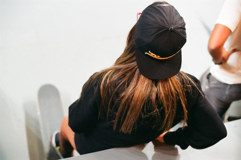 High Angle View Of Female With Skateboard Standing By Man