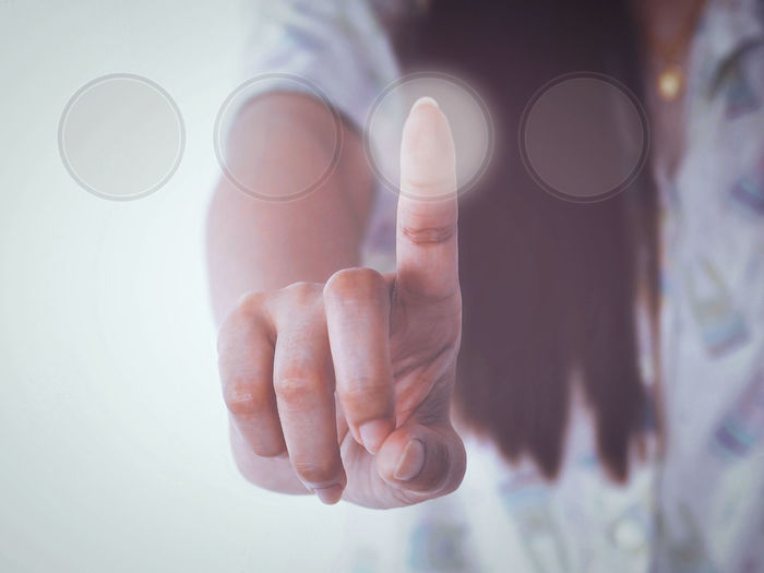 Digital composite image of woman touching button on invisible screen
