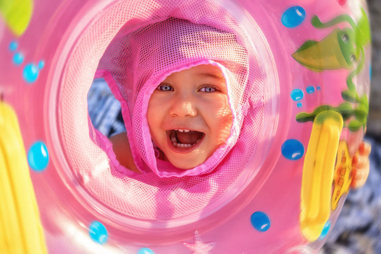 Close-up portrait of cute smiling girl with mouth open holding inflatable ring