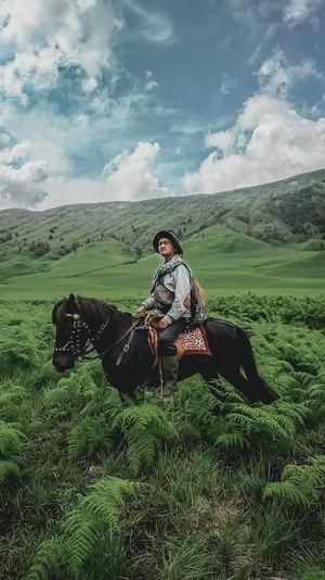 Man sitting on a horse in field