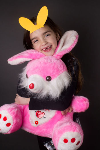 Girl embracing eater bunny stuffed toy against gray background