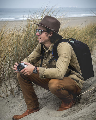One Person Real People Leisure Activity Young Adult Young Men Clothing Lifestyles Nature Looking Land Adult Sitting Casual Clothing Day Full Length Men Beard Field Outdoors Camera Felt Hat Boots Beach Ocean