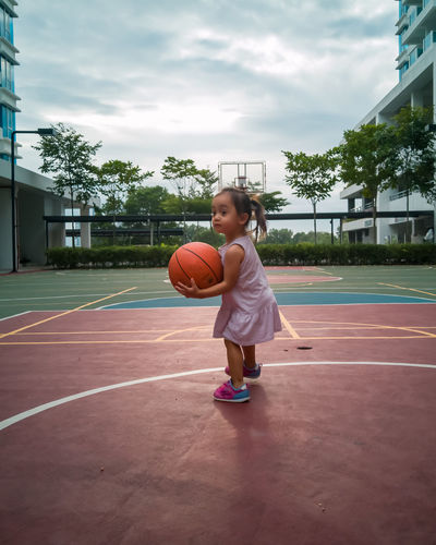 Full length of girl playing with basketball