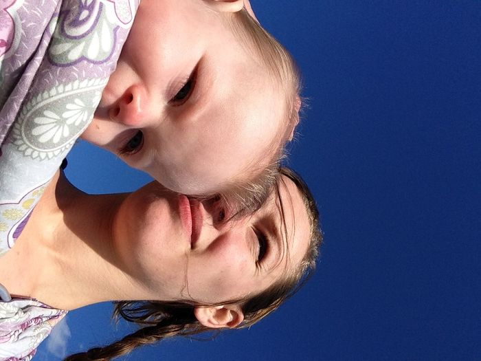 Low Angle View Of Mother With Child Against Clear Blue Sky