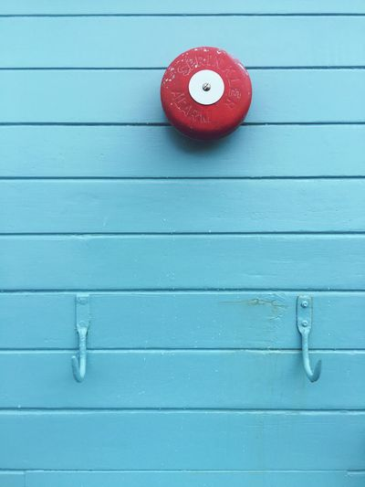 Red sprinkler alarm on the blue exterior wall Alarm Red Alarm Blue Wall Wooden Wall Alert