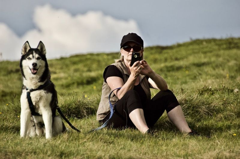 Woman using mobile phone with dog on field