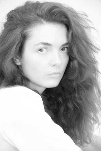 Close-up portrait of young woman against white background