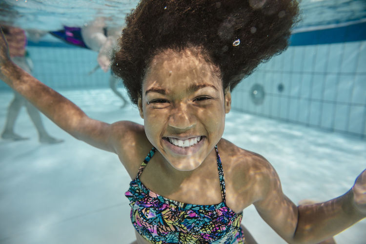 Portrait of a smiling young woman swimming pool