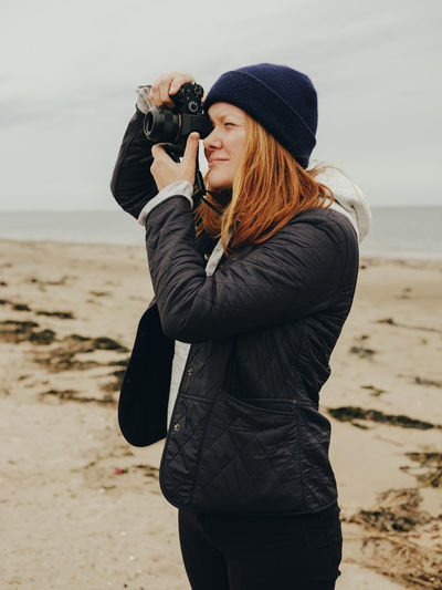 Young woman photographing while standing on beach