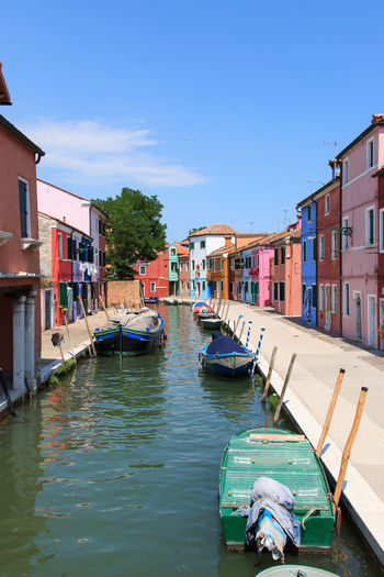 Boats anchored on canal by colorful houses