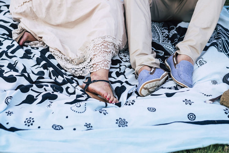 couple of hippy chic caucasian people lay down on a ethnic designed pareo with bright clothes and dress in outdoor leisure activity together Women Adult Real People Lifestyles Indoors  Human Body Part Two People High Angle View Human Hand Pattern Togetherness Clothing Leisure Activity Midsection People Tattoo Floral Pattern Fashion Wedding Dress Life Events Hand Wedding Ceremony Footpath barefoot Shoes Lying Down Outdoors Couple Caucasian Casual Clothing 35-39 Years 45-49 Years Hippie Bonding Relaxing Friendship