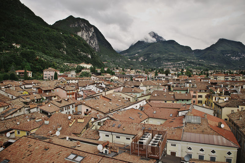 Townscape and mountains against cloudy sky