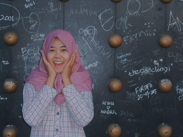 Portrait Of Surprised Teenage Girl Standing Against Blackboard In Classroom