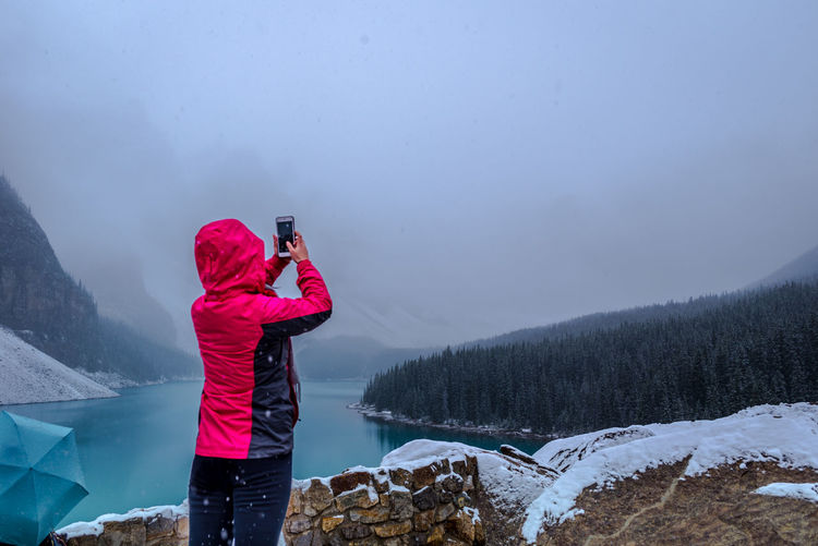 Rear View Of Woman Photographing During Winter