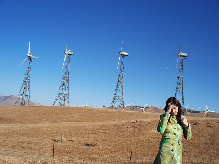 Woman standing on field against clear blue sky