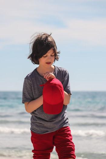 Cute boy with cap standing at beach