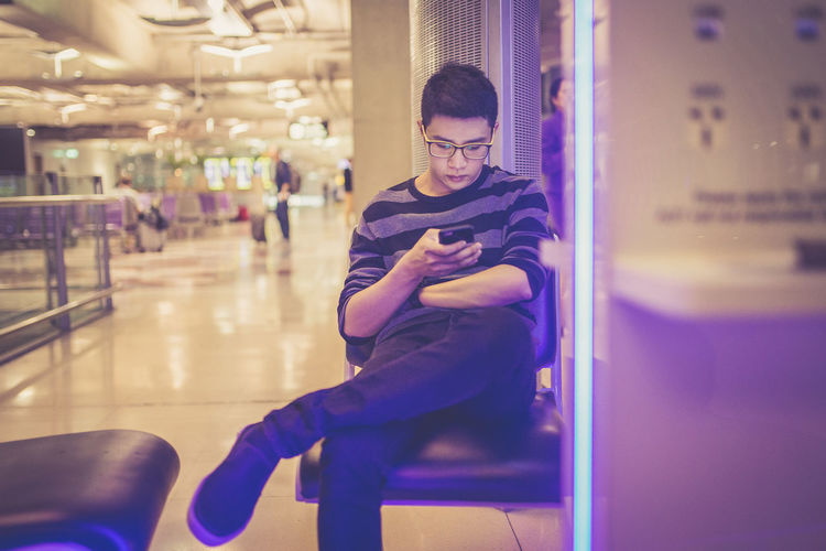 Man using mobile phone while sitting at airport