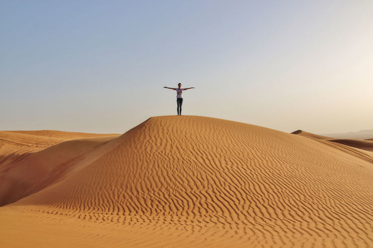 View Of Woman In Desert Against Clear Sky