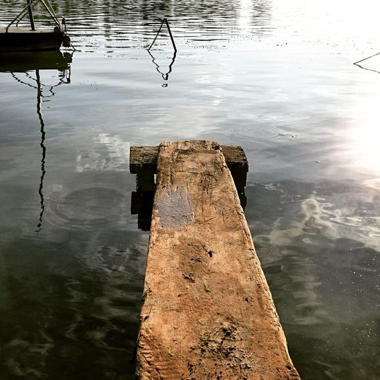 High angle view of wooden post in lake against sky