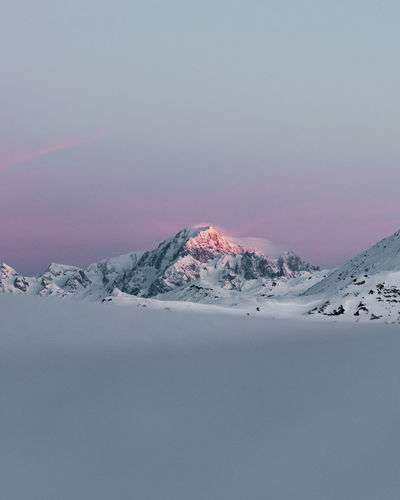 Scenic view of snowcapped mountain against sky during sunset