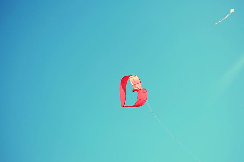 Low Angle View Of Heart Shape Kite Flying Against Clear Blue Sky
