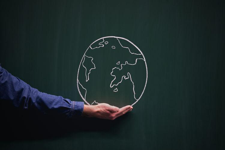 Optical illusion of hand holding earth on blackboard