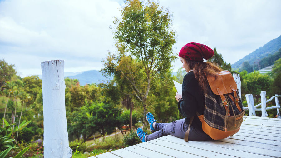 Rear view of woman wearing knit hat sitting on plank against sky