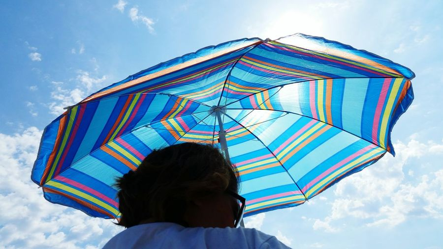 Woman with umbrella against sky in sunny day