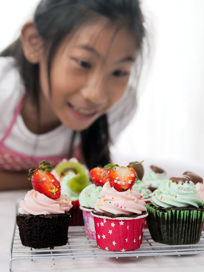 Close-up of girl looking at cupcakes on cooling rack