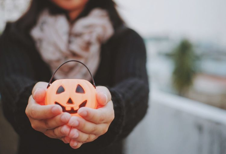 Midsection of woman showing jack o lantern toy during halloween