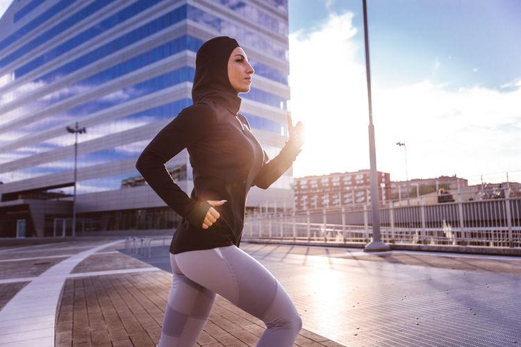 Full length of man running in city against sky