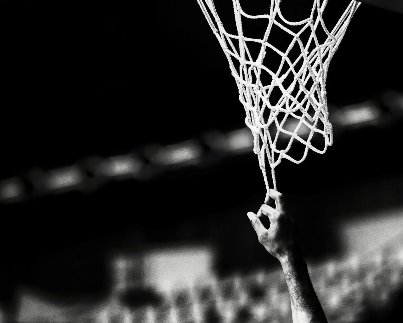 CLOSE-UP OF HUMAN HAND AGAINST BASKETBALL HOOP