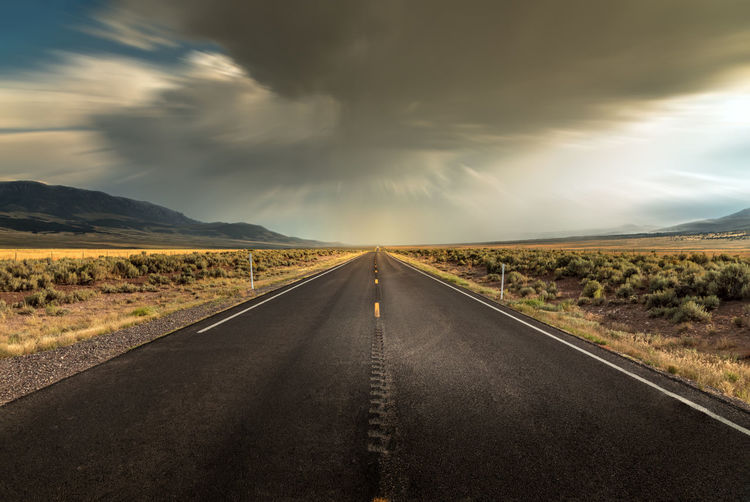 Long straight road in utah with dramatic clouds and rain rolling in