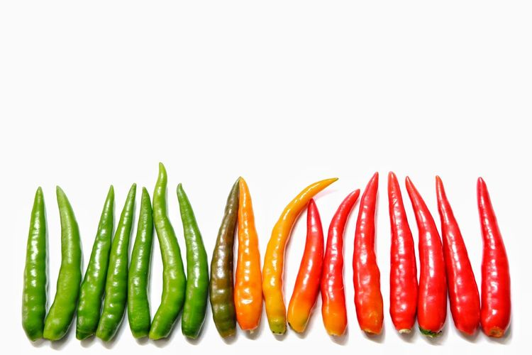 Close-up of multi colored chili peppers against white background
