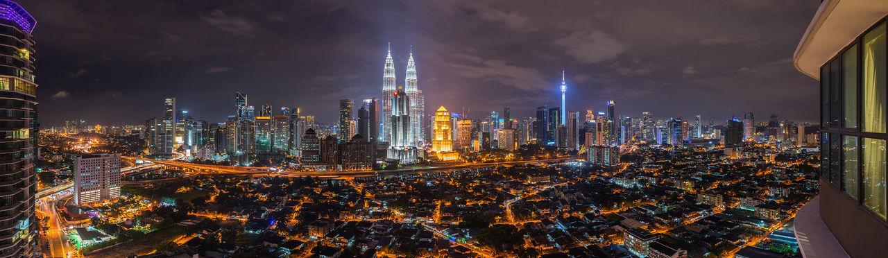 Panoramic shot of illuminated petronas towers in city at night