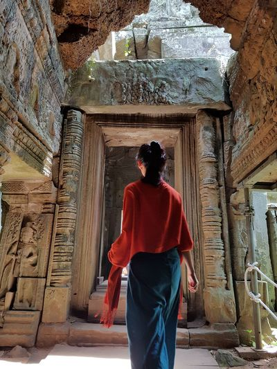Rear view of woman standing in old ruin temple