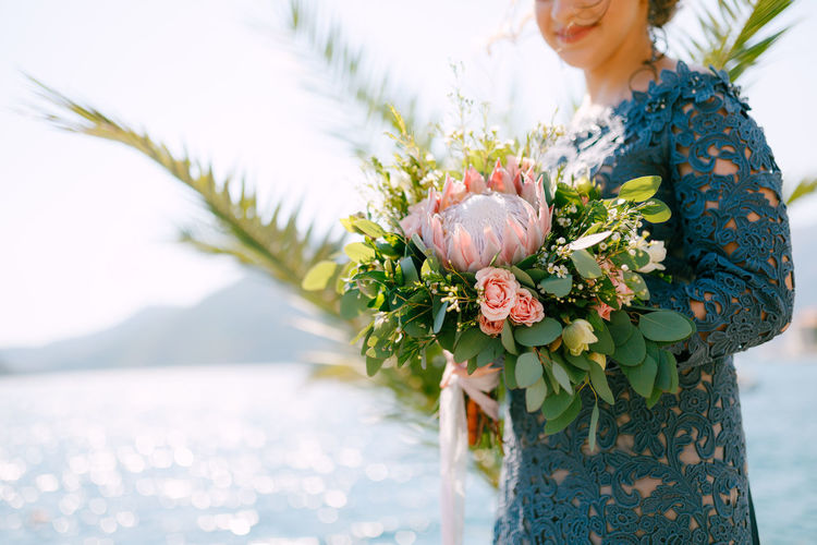 Midsection of woman standing by flowering plant in sea