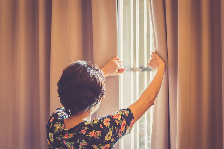 Woman opened curtain in living room. Boys Childhood Close-up Curtain Day Holding Home Interior Indoors  Lifestyles One Person People Real People Rear View Standing