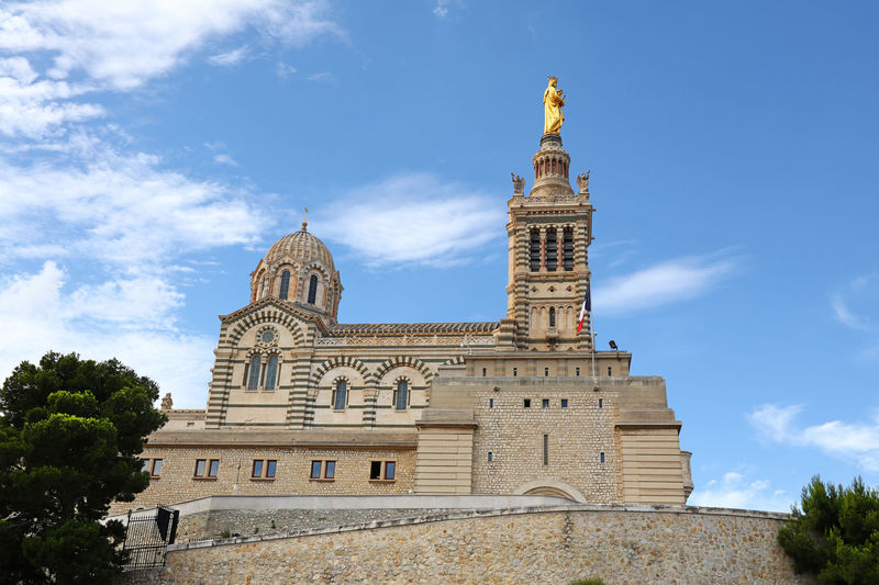 Notre-Dame de la Garde (Our Lady of the Guard) cathedral in Marseille Notre-dame De La Garde Spire  Ornate Outdoors No People Tourism The Past History Day Travel Destinations Travel Cloud - Sky Tower Place Of Worship Low Angle View Religion Building Building Exterior Built Structure Sky Architecture Cathedral Basilica Landmark Famous Place